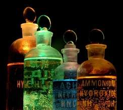 Solutions of substances in reagent bottles, including ammonium hydroxide and nitric acid, illuminated in different colors