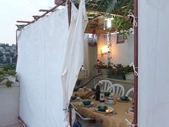 Canvas-sided sukkah on a roof, topped with palm branches and bamboo s'chach