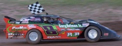 Late model stock car driver celebrates with a chequered flag