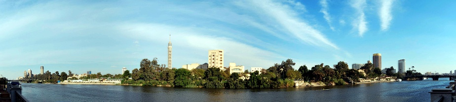 A panorama of the Nile in central Cairo showing the west side of Gezira Island, located in the middle of the Nile, with the Cairo Tower in the middle, the 6th October Bridge on the far left and El Galaa Bridge on the far right