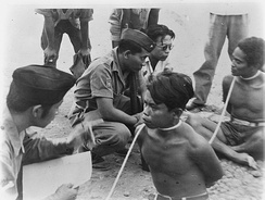 Two men with rope around their necks are handcuffed by TNI officers in September 1948 in Madiun, Indonesia.
