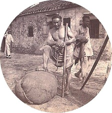 Coolie labourer in Zhenjiang, China, with bamboo pole to hoist and carry heavy loads.C. 1900