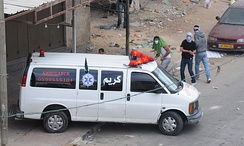"Palestinian rioters in Qalandiya throw rocks from behind an ambulance during a riot as part of the ""Nakba"" protests."