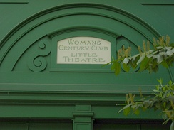 A sign over the rear door of the Harvard Exit Theatre recognizing the Woman's Century Club, founded in 1891. The club constructed the building in 1925 to serve as its clubhouse; it is now the Mexican consulate