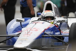 Photograph of Wilson sitting in his blue and white racing car in the pit at the 2015 Indianapolis 500