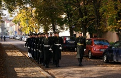 Lithuanian Army soldiers marching with their dress uniforms in Vilnius. An officer stands out with a sword.