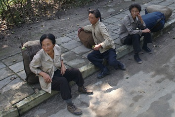 A group of aged women with full backpacks sitting on the street.