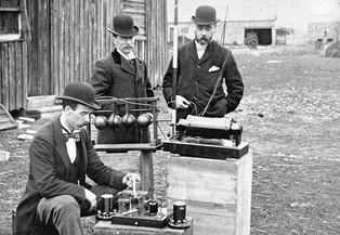 British Post Office engineers inspect Marconi's radio equipment during a demonstration on Flat Holm Island, 13 May 1897.  The transmitter is at centre, the coherer receiver below it, and the pole supporting the wire antenna is visible at top.