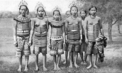 Sea Dayaks (Iban) women from Rejang, Sarawak, wearing rattan corsets decorated with brass rings and filigree adornments. The family adds to the corset dress as the girl ages and based on her family's wealth.