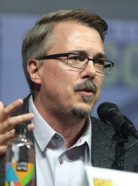 A man with dark brown hair, sporting rectangular glasses, a mustache and goatee while wearing a teal shirt and dark grey glasses, looks to the right while speaking into a microphone.