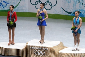 Kim (center) with Mao Asada (left) and Joannie Rochette (right) on the 2010 Winter Olympics podium.