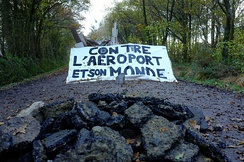 A barricade at the ZAD de Notre-Dame-des-Landes (2012). Banner reads: Against the airport and its world.