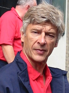 In front of building entrance, a white-haired man with a red polo shirt under a dark blue coat looks straight at the camera.