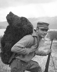 A hunter with the head of a Kodiak bear on his back