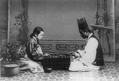 Korean couple, in traditional dress, play in a photograph dated between 1910 and 1920