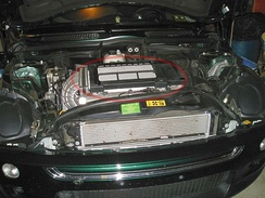 The engine bay of a 2003 MINI Cooper S. The top-mounted intercooler is circled in red.