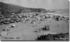 Black and white photograph of a beach covered in tents
