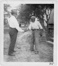 "John Lomax (left) shaking hands with musician ""Uncle"" Rich Brown in Sumterville, Alabama"