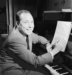 Johnny Mercer in front a piano, holding a pen.