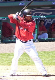 Batter in black hat red top and white pants, batting during spring training for the Red Sox.