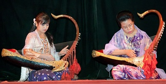 Two female musicians play the saung at a performance in Mandalay.