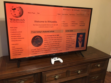 A flatscreen TCL TV on its stand, on top of a drawers table, HDMI-connected to a Windows computer which has Controller Companion, enabling it to use a Bluetooth-connected Xbox One controller as a remote input device. The blue light-filtered screen displays Wikipedia's homepage.