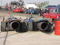 Dual braking parachutes fitted to jet dragsters. The parachutes are in the smaller tubes with yellow straps.