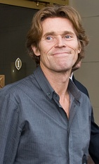 A portrait of Willem Dafoe wearing a blue shirt.