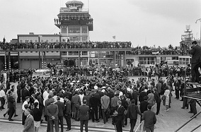 Fans and media swarm the Beatles at Schiphol Airport in 1964.