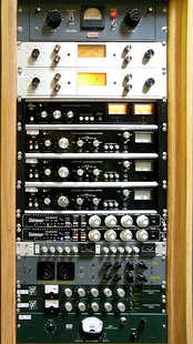 A rack of audio compressors in a recording studio. From top to bottom: Retro Instruments/Gates STA level; Spectra Sonic; Dbx 162; Dbx 165; Empirical Labs Distressor; Smart Research C2; Chandler Limited TG1; Daking FET (91579); and Altec 436c.