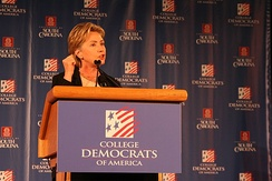 Photograph of Clinton speaking at a lectern to the College Democrats