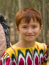 Uyghur girl in clothing made of fabric with design distinctive to the Uyghurs