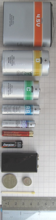 From top to bottom: a large 4.5-volt 3R12 battery, a D Cell, a C cell, an AA cell, an AAA cell, an AAAA cell, an A23 battery, a 9-volt PP3 battery, and a pair of button cells (CR2032 and LR44)