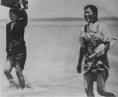 Comfort women crossing a river following soldiers.