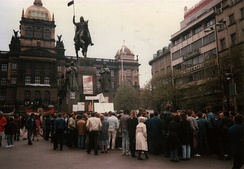 Prior to the June 1990 elections, demonstrators on Wenceslas Square in April gather under a poster where the red star and initials of the KSČ has a swastika painted on top of it while the coat of arms depicted is from before the formation of the Czechoslovak Socialist Republic