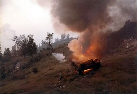 A Syrian tank burning on the road outside Jezzine