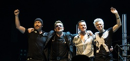 U2 take a curtain call during a 7 November 2015 performance on the Innocence + Experience Tour (from left to right): the Edge, Bono, Mullen, Clayton