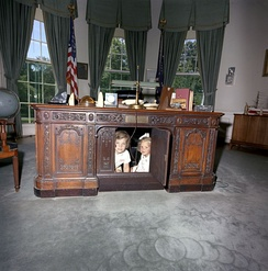 Caroline Kennedy and Kerry Kennedy beneath the Resolute desk in 1963