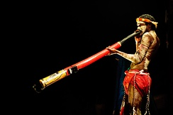 An Indigenous Australian playing the didgeridoo.