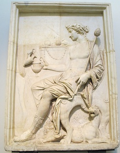 Ancient Roman relief in the Museo Archeologico (Naples) depicting Dionysus holding a thyrsus and receiving a libation, wearing an ivy wreath, and attended by a panther.
