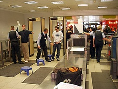 Baggage is scanned using X-ray machines as passengers walk through metal detectors
