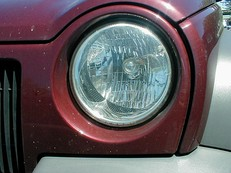A reflector-optic headlamp on a Jeep Liberty. The clear front cover lens serves only a protective function.
