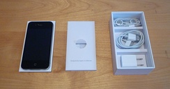 The contents of the box of an iPhone 4. From left to right: iPhone 4 in plastic holder, written documentation, and (top to bottom) headset, USB cable, wall charger.