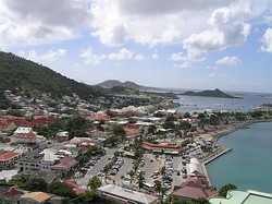 A village on the coast of an island. Small buildings are located throughout the island, with mountains in the background and the ocean on the right. Among the buildings in the foreground is a parking lot adjacent to a marina. A peninsula stretches out into the ocean and boats are on the ocean in the background.