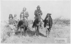 """Geronimo's camp before surrender to General Crook, March 27, 1886: Geronimo and Natches mounted; Geronimo's son (Perico) standing at his side holding baby."" By C. S. Fly."