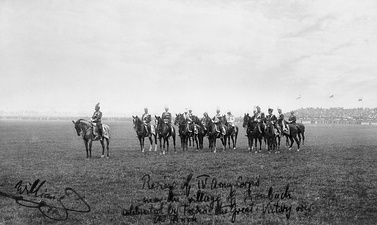 Old photograph showing men on horseback standing in a field.