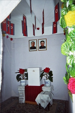 A North Korean voting booth containing portraits of Kim Il-sung and Kim Jong-il under the national flag (below the portraits is the ballot box)