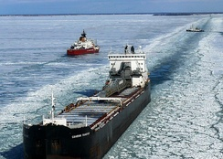 Channel through ice for ship traffic on Lake Huron with ice breakers in background