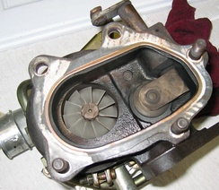 An internally gated turbocharger. The internal gate is located to the right of the turbine wheel, but built into the turbine housing. Partially seen at the top is the wastegate.