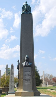 A large obelisk in a graveyard, with a bust of Tyler, and a black cast iron cage partially visible behind it.